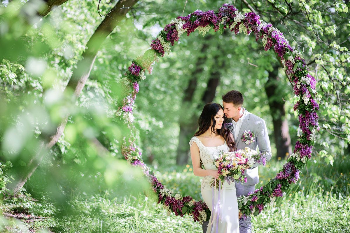 Bride and groom pose behind large circle of lilac in the garden